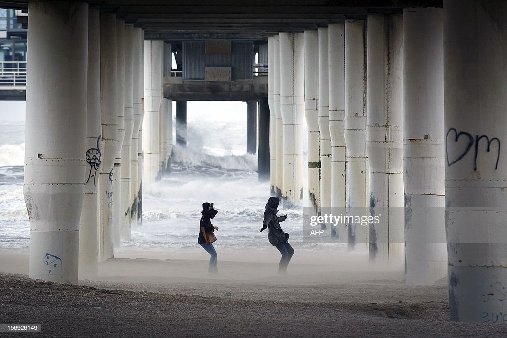Walkers on the beach at the coastal town of Scheveningen, near The Hague,struggle against the wind on November 25, 2012. A storm rants about the Netherlands, especially in the coastal provinces with gusts of wind and wind force nine.