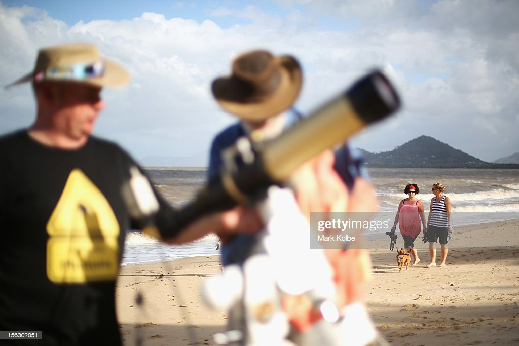Walkers pass as telescopic cameras and computer equipment are set up on Palm Cove beach in preparation to run a live stream via NASA of the total solar eclipse on November 13, 2012 in Cairns, Australia. Thousands of eclipse-watchers have gathered in part of North Queensland to enjoy the solar eclipse, the first in Australia in a decade.