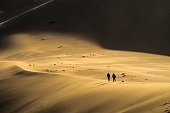 Two men walk up a giant sand dune in the Gobi Desert, Mongolia.