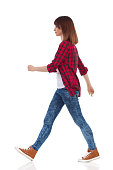 Woman in red lumberjack shirt, jeans and brown sneakers walking and looking away. Side view. Full length studio shot isolated on white.