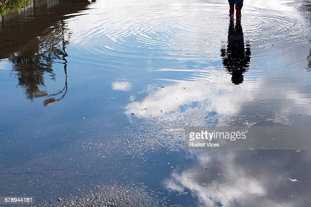 Walking child and sky reflection in a puddle