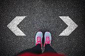 Woman standing on asphalt looking down at arrow sign on asphalt and her choosing,