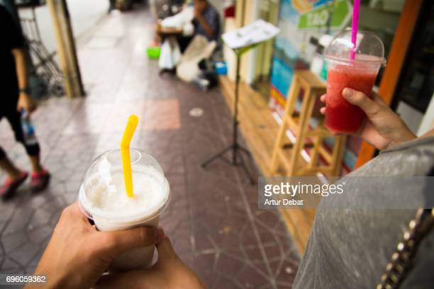 Walking from personal perspective in Bangkok city cooling off with natural fruit milkshake during travel vacations in the city.