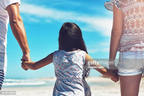Walking hand-in-hand with her parents