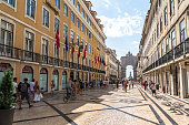 Walking in central street with view on big arch, Portugal