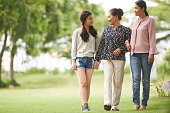 Cheerful Vietnamese teenage girl with her mother and grandmother walking in park