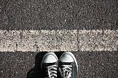 People shoes standing on the asphalt with white line.