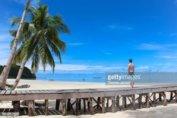 Walking on a wooden jetty surrounded by blue sky and beautiful beach, Carp Island, Palau