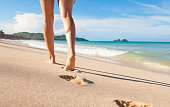 Woman walking on the beach in Hawaii. Summer travel concept.