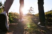 Human legs of couple walking on path, sun shining
