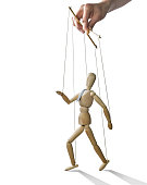 Puppet in the hands of puppeteer walks on isolated, white background.  Puppet is presented in business style with a tie.