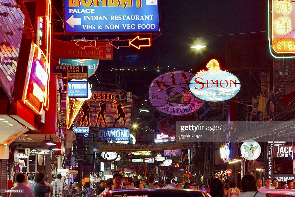 Walking street at night with tourists and go-go bars.