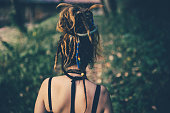 Rear View Of Dread-haired Girl Exploring Wild Forest On Hot Day