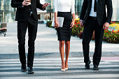 Cropped image of three business people crossing the street