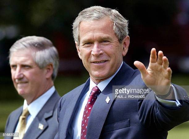 Walking towards Marine One with his White House Chief of Staff Andrew Card at his side US President George W Bush waves to reporters yelling...