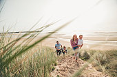 Family with two little boys walking up the sand dune.