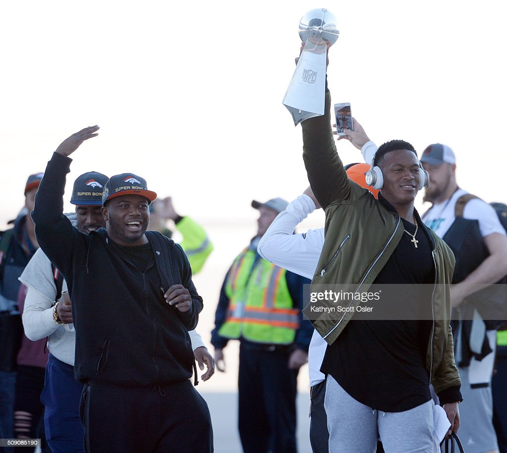 Walking with C.J. Anderson, Demaryius Thomas, right, holds up the Vince Lombardi Tophy as members of the Denver Broncos football team arrive home at Denver international Airport on Monday, Feb. 8, 2016.