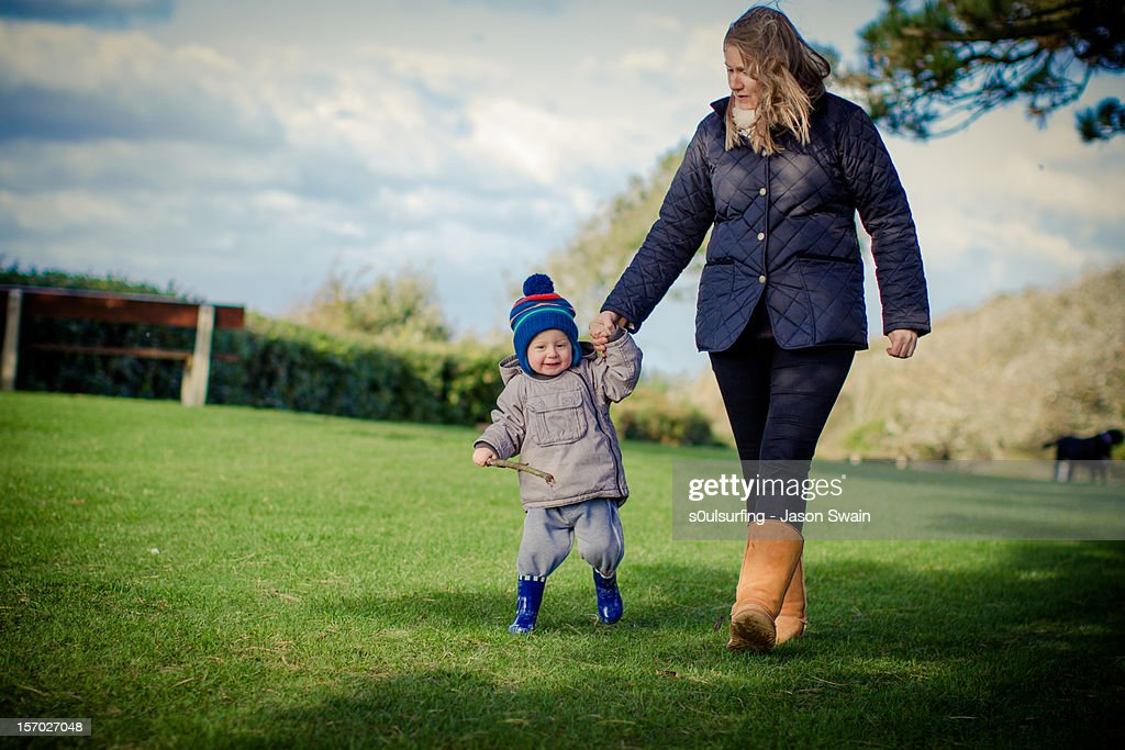 Walking with mum in the park : Stock Photo