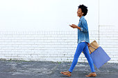 Side portrait of a smiling young woman walking with shopping bags and listening to music on smart phone