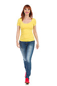 Young woman in yellow shirt, jeans and red sneakers is walking towards camera and smiling. Front view. Full length studio shot isolated on white.