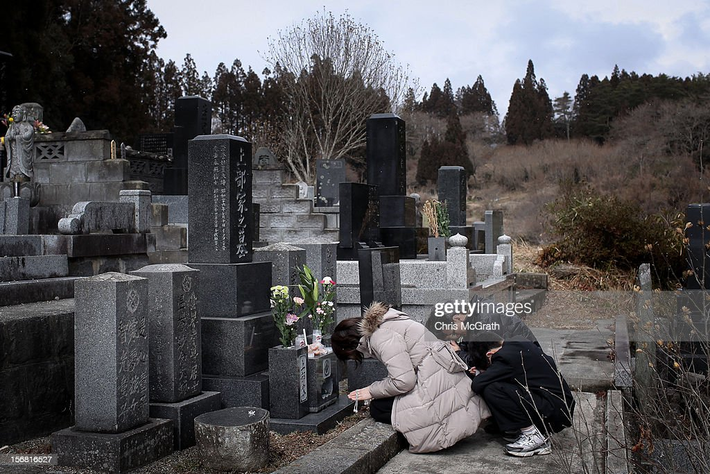 Walkley Press Photographer of The Year Portfolio on November 22, 2012 in Singapore. Image Caption: Keiko Takeda, husband Yoshihiro and two son's Seiya and Shunma pray at the gravesite of her parents, Tetsji and Hiroko and uncle Hiroo and aunt Moto at the Jodoji Temple on March 11, 2012 in Rikuzentakata, Japan. On the one year anniversary, the areas most affected by last year's March 11, 2011 earthquake and subsequent tsunami that left 15,848 dead and 3,305 missing according to Japan's National Police Agency, continue to struggle. Thousands of people still remain without homes living in temporary dwellings. The Japanese government faces an uphill battle with the need to dispose of rubble as it works to rebuild economies and livelihoods. Across the country people are taking part in ceremonies to pay respects to the people who lost their lives.