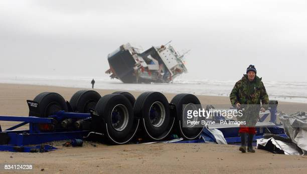 A walks past the wheels of a container lorry that has fallen from the Irish ferry 'Riverdance' which ran aground last weekend and can be seen in the...