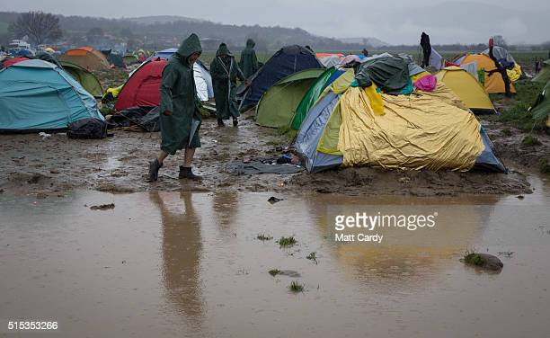 A walks stands besides tents close to standing water that has developed due to heavy rain fall at the Idomeni refugee camp on the Greek Macedonia...
