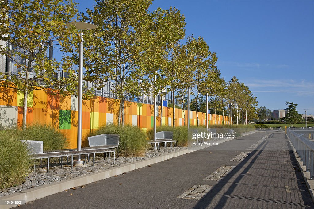 Walkway near trees, benches and colorful wall. : Stock Photo