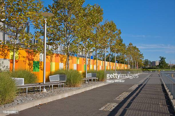 Walkway near trees, benches and colorful wall.