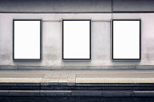 Three blank posters on a wall by a station platform. Includes clipping paths.