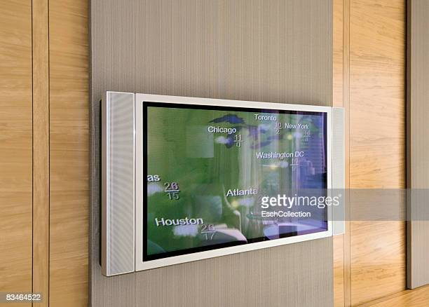 Wall and flat screen television displaying weather