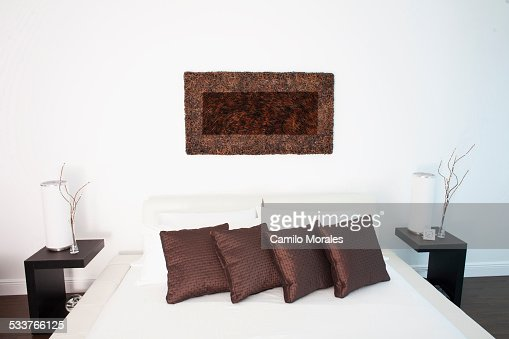 wall art night tables and bed in modern bedroom stock photo