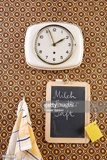 A wall clock, dish towel and chalkboard, still life