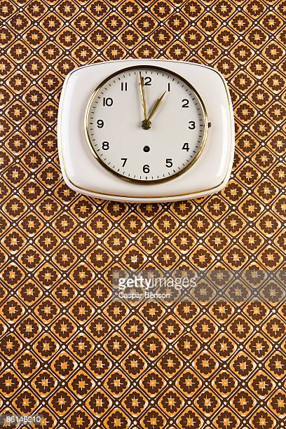 A wall clock hanging on patterned wallpaper