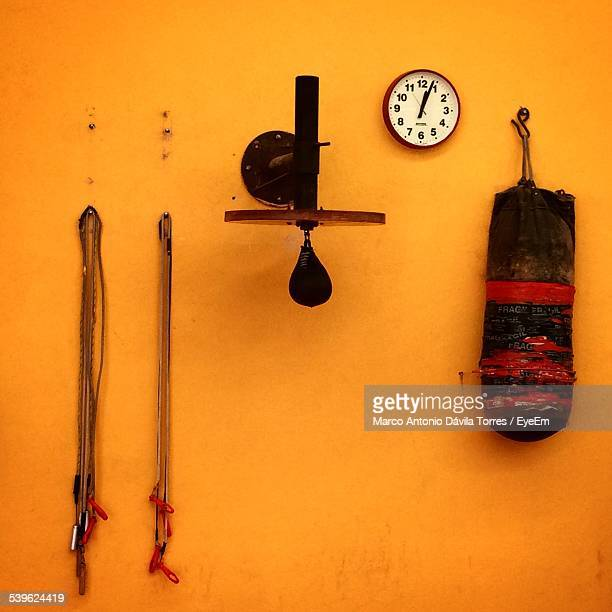Wall Clock With Boxing Equipment Handing On Orange Wall