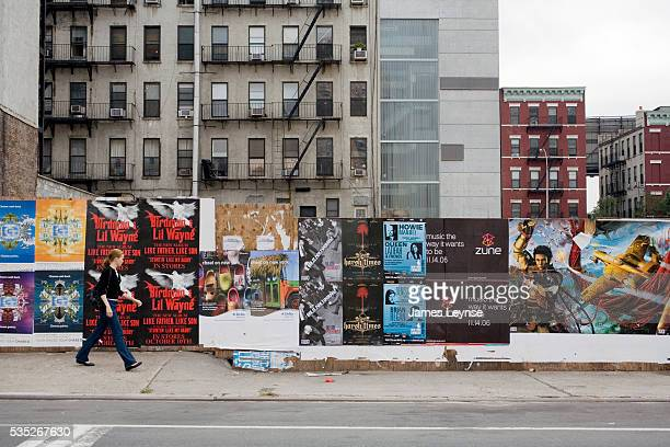 A wall covered with posters on a street in New York