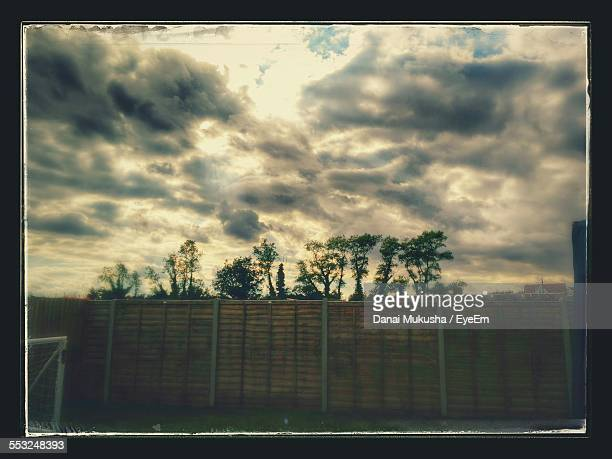 Wall In Front Of Trees Against Cloudy Sky