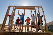 A wall is raised on a Habitat for Humanity house being built to replace one that was destroyed one year ago today after the town was hit by a...