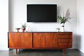 A 50 inch flat screen TV wall is mounted above a mid century modern teak credenza. Decorated with simple, modern pottery, plants, candle and aromatherapy.