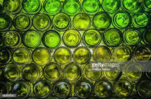 Wall of empty green wine bottles