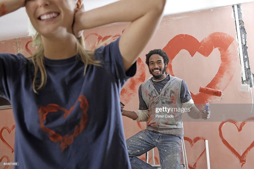 wall painted with hearts, woman walking away : Stock Photo