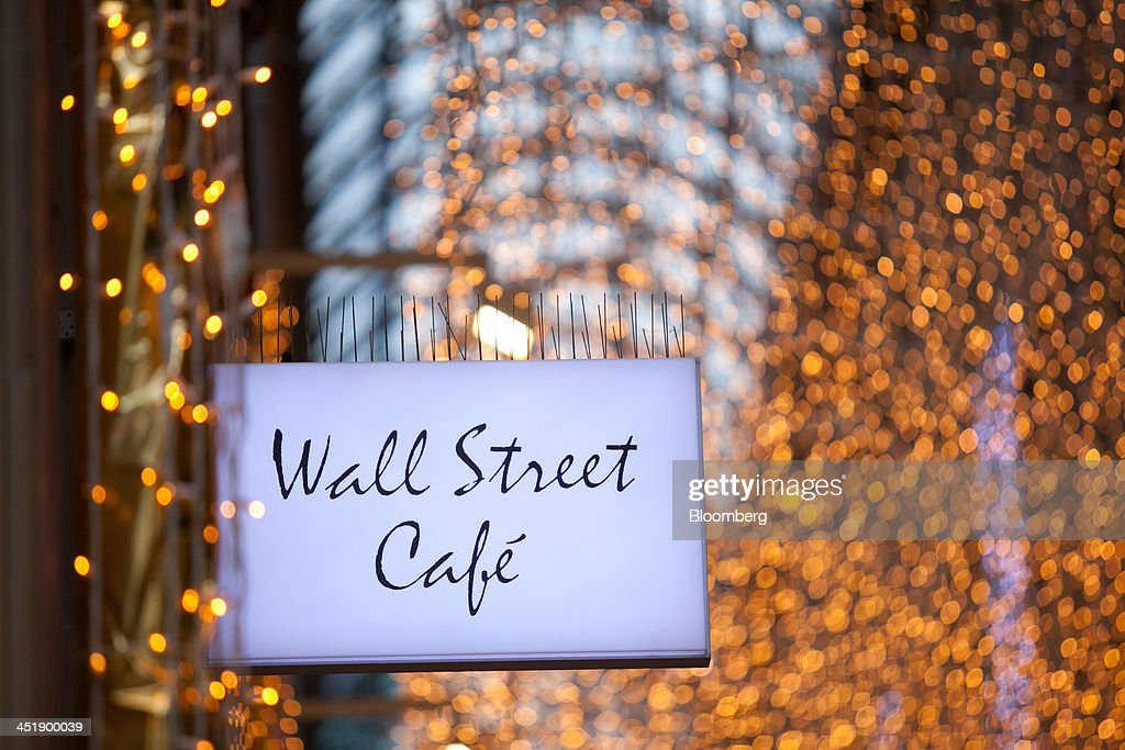 A 'Wall Street Cafe' sign sits on display as festive lights hang inside Kaufingertor Passage shopping arcade in Munich, Germany, on Sunday, Nov. 24, 2013. In Germany, Europe's biggest economy, annual consumer prices increased 1.2 percent in October. Photographer: Krisztian Bocsi/Bloomberg via Getty Images