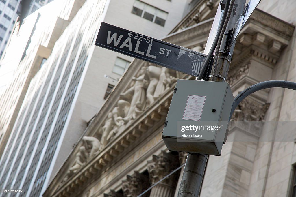 A Wall Street sign is displayed outside the New York Stock Exchange (NYSE) in New York, U.S., on Friday, Feb. 12, 2016. U.S. stocks halted a five-day slide that dragged global equities into a bear market, as oil rebounded from a 12-year low and bank shares surged. Photographer: Michael Nagle/Bloomberg via Getty Images