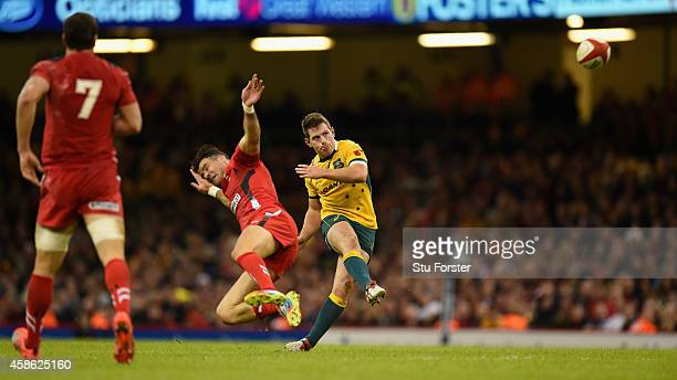 Wallabies fly half Bernard Foley kicks a drop goal despite the attentions of Mike Phillips during the Autumn international match between Wales and...