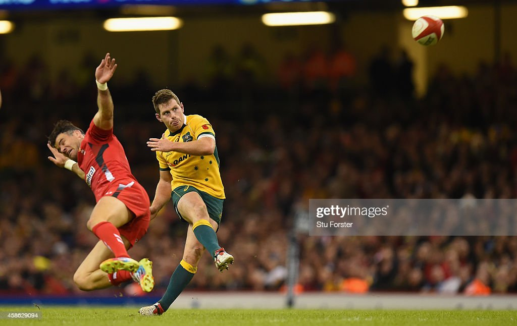 Wallabies fly half <a gi-track='captionPersonalityLinkClicked' href=/galleries/search?phrase=Bernard+Foley&family=editorial&specificpeople=6563906 ng-click='$event.stopPropagation()'>Bernard Foley</a> kicks a drop goal despite the attentions of Mike Phillips during the Autumn international match between Wales and Australia at Millennium Stadium on November 8, 2014 in Cardiff, Wales.
