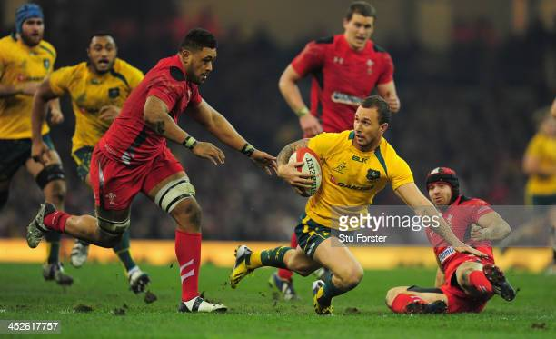 Wallabies fly half Quade Cooper evades the tackle of Leigh Halfpenny of Wales during the International match between Wales and Australia Wallabies at...