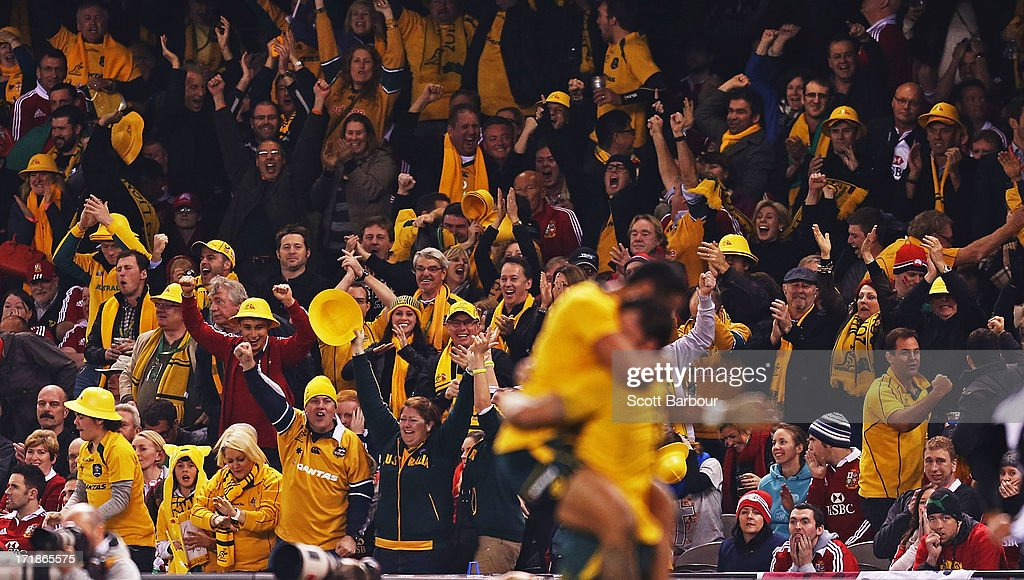 Wallabies supporters celebrate in the crowd as Adam Ashley-Cooper of the Wallabies celebrates with team mate Christian Lealiifano of the Wallabies after scoring a try during game two of the International Test Series between the Australian Wallabies and the British & Irish Lions at Etihad Stadium on June 29, 2013 in Melbourne, Australia.