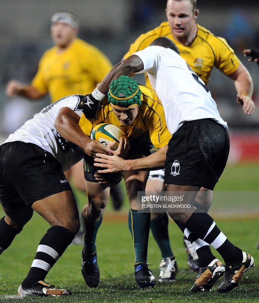 Wallaby centre Matt Giteau (C) tries to break through the Fijian defence during the Australia v Fiji rugby union Test in Canberra on June 5, 2010. Australia thrashed Fiji 49-3. AFP PHOTO / Torsten BLACKWOOD