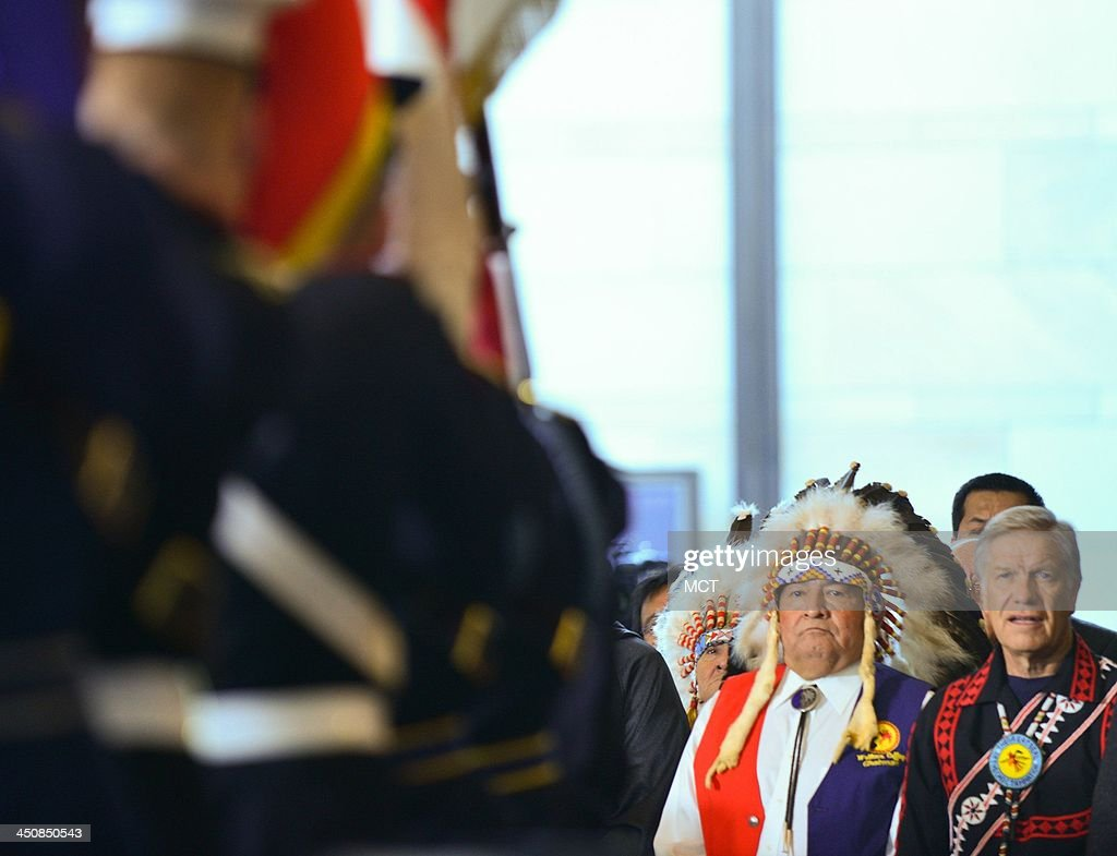 Wallace Coffey, right, Chairman of the Comanche Nation, back left, and other attendees watch the honor guard enter on Wednesday, Nov. 20, 2013, in Washington, DC, during a ceremony awarding the Congressional Gold Medal to Native American Code Talkers who served in the military providing critical communication skills.