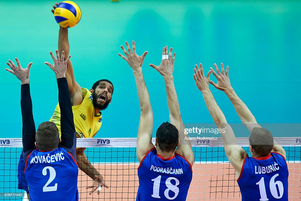 Wallace De Souza from Brazil spikes against Uros Kovacevic from Serbia and Marko Podrascanin from Serbia and Drazen Luburic from Serbia while the...